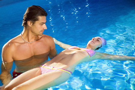 lifeguard: Healthy lifestyle: girl taking swimming lessons in a swimming pool