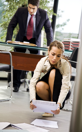 fatigued: Office life: exhausted secretary picking up some files   Stock Photo