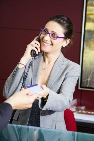 oficinista: Pagar con tarjeta de cr�dito: salesclerk joven sonriente a un cliente  Foto de archivo