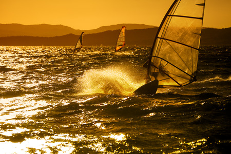 summer sports: windsurfer speeding fast against the sunset