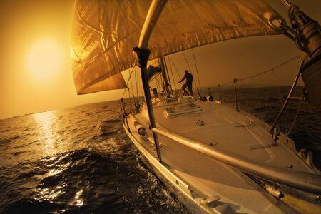 bateau voile: personnes sur une voile en bateau au coucher du soleil.  Banque d'images