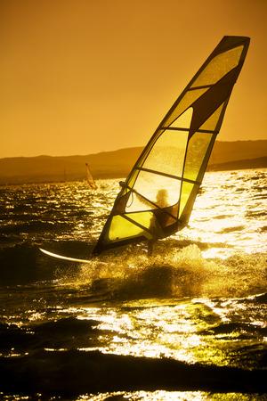 liveliness: summer sports: windsurfer speeding fast against the sunset  Stock Photo