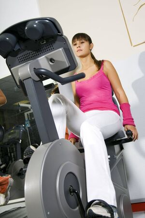 health club: health club: young girl working out on a cyclette Stock Photo
