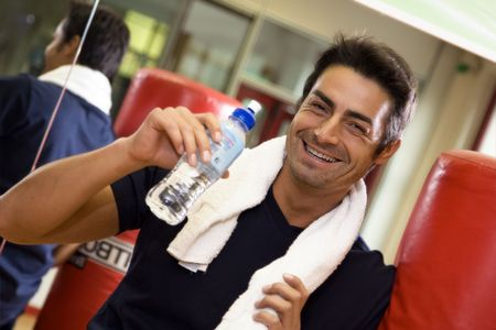 health club: health club: athlete relaxing and drinking some water