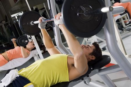 Man and woman in a gym doing weight lifting