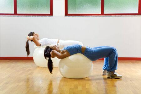 Mujeres haciendo estiramientos y ejercicios aeróbicos en pelota de goma  Foto de archivo - 1884425