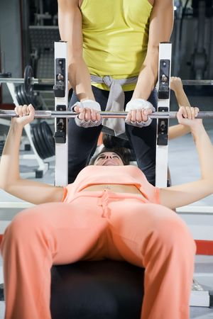 health club: girl in a gym doing weight lifting photo