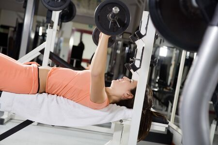 endure: health club: girl in a gym doing weight lifting