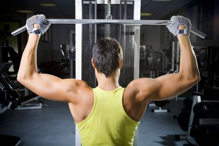 health club: man in a gym doing weight lifting photo