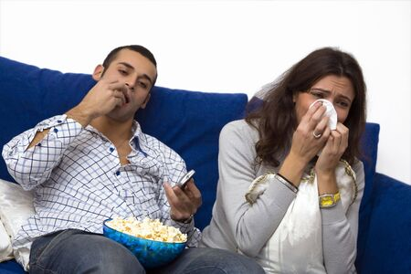 indifferent: young couple watching a  movie on tv. The guy is quite bored.... Stock Photo