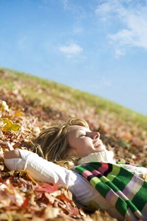 expressing: expressing positivity: blond girl resting on autumn leaves