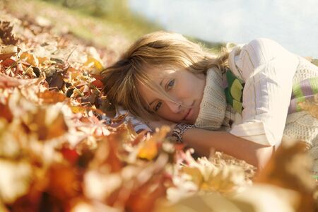 expressing positivity: blond girl resting on autumn leaves Stock Photo - 2066619