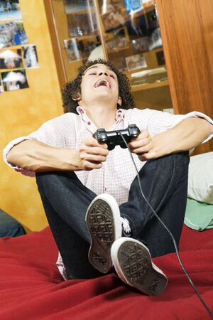 passtime: playing video games: guy feet crossed on the bed having fun with his brand new videogame