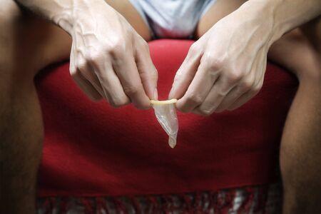 hombre desnudo: hombre desnudo con un preservativo en sus manos  Foto de archivo