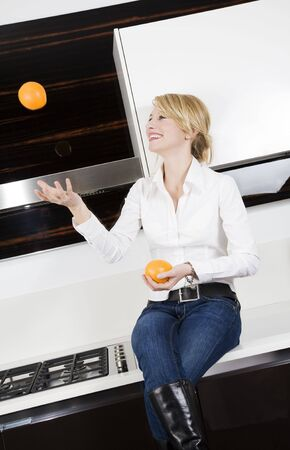 home life: woman relaxing and playing with oranges Stock Photo - 2206540