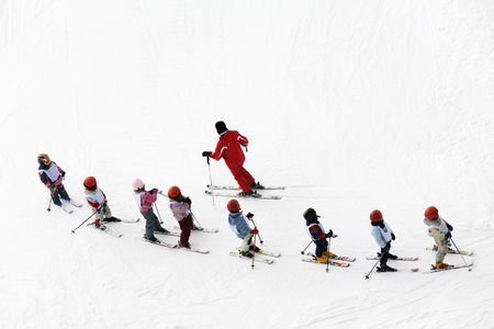 skiers: winter scene: kids learning to ski and their instructor