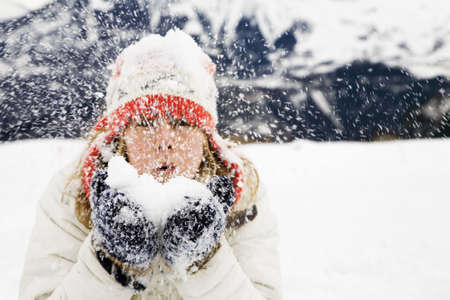 winter scene: girl blowing snow away. The focus is on the gloves. photo