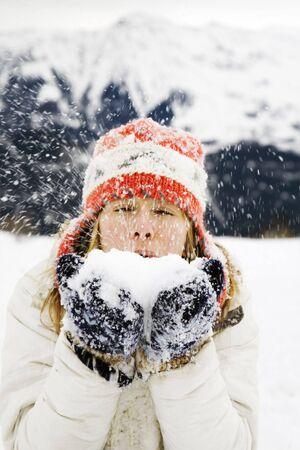 having fun in winter time: winter scene: girl blowing snow away. Stock Photo