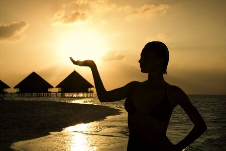 tropical beach: beautiful girl holding the sun in her hands photo