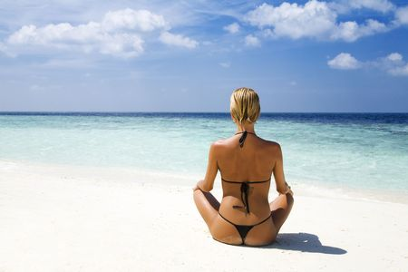 vacationing: tropical beach: perfect girl meditating on a tropical beach. Copy space Stock Photo