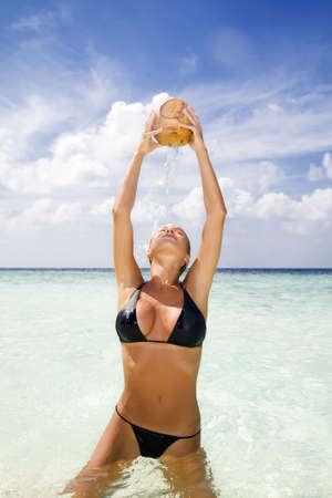tropical beach: beautiful girl drinking from a coconut in her hands photo