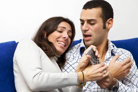 hostility: young couple watching tv and fighting to get the remote control Stock Photo
