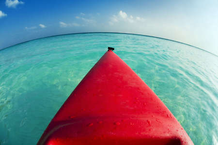 vacationing: tropical beach: red canoa on the seashore