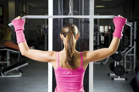 sudando: club de salud: las niñas en un gimnasio haciendo levantamiento de pesas  Foto de archivo