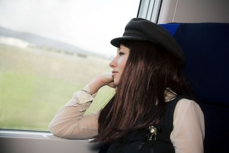 vacationer: nice girl sitting on a train and looking out of the window