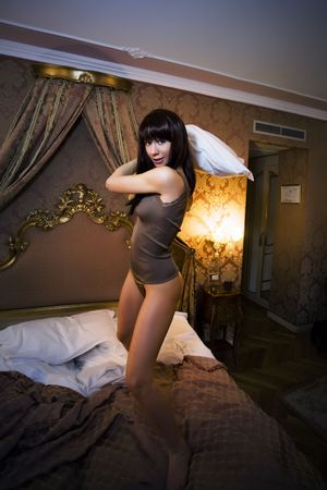 woman playing pillow fight on bed photo