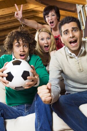 domestic life: group of friend watching soccer on tv Stock Photo