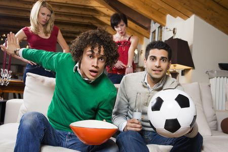 domestic life: group of friend watching soccer on tv while their girlfriends are disappointed