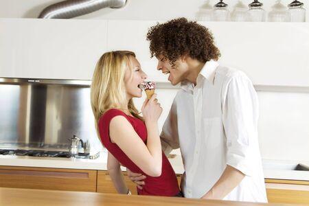 pareja comiendo: la vida dom�stica: interracial pareja comiendo un helado  Foto de archivo