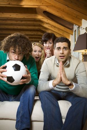 domestic life: domestic life: group of friends watching a football match on tv Stock Photo