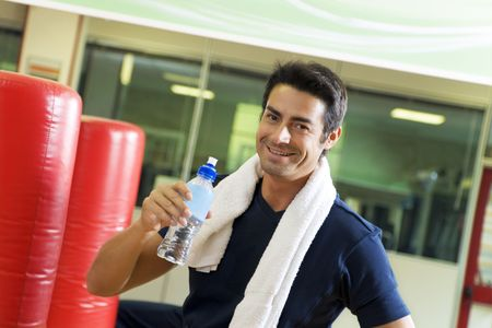 sweating: health club: athlete relaxing and drinking some water   Stock Photo