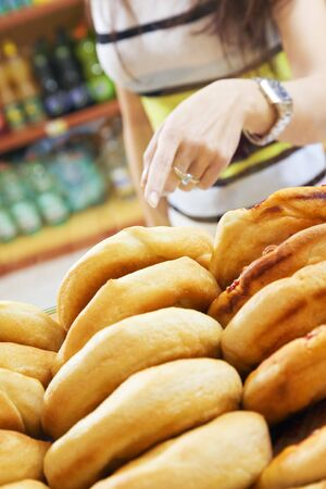 bakery store: customer in a supermarket buying a slice of pizza