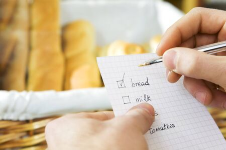 customer in a supermarket checking his shopping list
