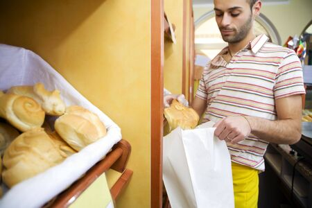 sales clerk in a supermarket putting some bread in a bag Stock Photo - 2738230