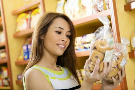 gluten: woman in a supermarket reading nutrition information and comparing two products