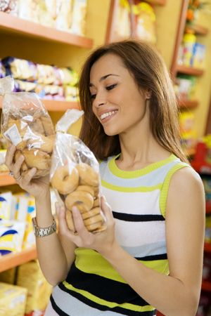 woman in a supermarket reading nutrition information and comparing two products photo