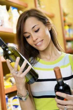 woman in a supermarket comparing two wines photo