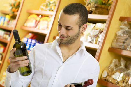 man in a supermarket comparing two wines Stock Photo - 2757658