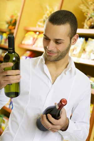 man in a supermarket comparing two wines Stock Photo - 2757674