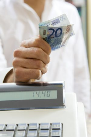 20 euro: man at the supermarket standing near the cash box and holding 20 Euro Stock Photo