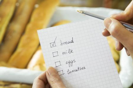 hacer: Mujer en un supermercado de la comprobación de su lista de compras