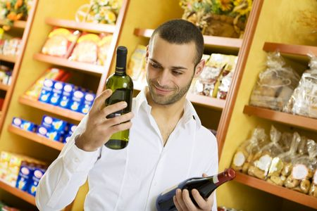man in a supermarket comparing two wines photo