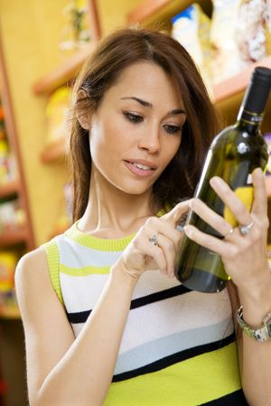 woman in a supermarket reading the label behind a bottle of wine photo