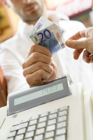 cash register: man at the supermarket giving 20 Euro to the cashier