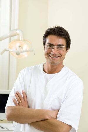 dentist with arms folded smiling and standing in his office photo