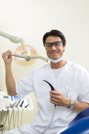 medical lighting: dentist turning on examination light Stock Photo